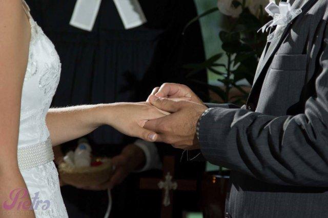 Noivo colocando aliança na noiva