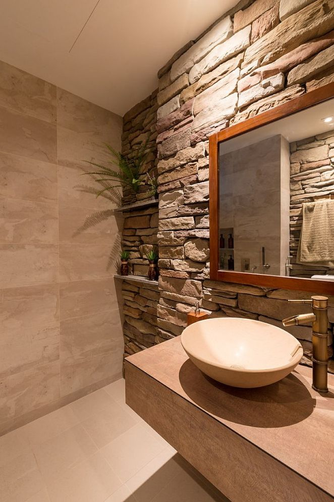 Tropical-style-powder-room-with-a-stacked-stone-wall