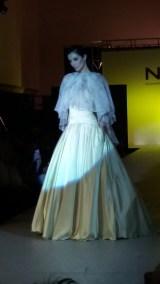 Vista frontal de vestido con falda con bolsillos y vuelo, entallada a la cadera, y top asimétrico tipo capa en tejido semitransparente. ALICIA ARZA.