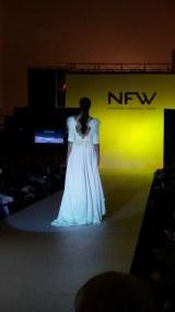 Vista trasera de vestido con escote pronunciado en la espalda, manga francesa, detalles en hombros y caderas y falda con aberturas. ALICIA ARZA.