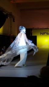 Vista en movimiento de chubasquero de PVC con plumas y capucha. ALICIA ARZA.