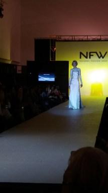 Vista delantera de vestido de manga larga en tela brillante, cuerpo ajustado, abertura lateral y espalda abierta. ALICIA ARZA.