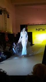 Vista frontal de chubasquero de plástico con detalles bordados y vestido de pedrería. ALICIA ARZA.