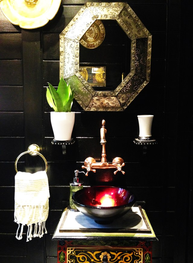 Black global style bathroom with eclectic styling and gold accents