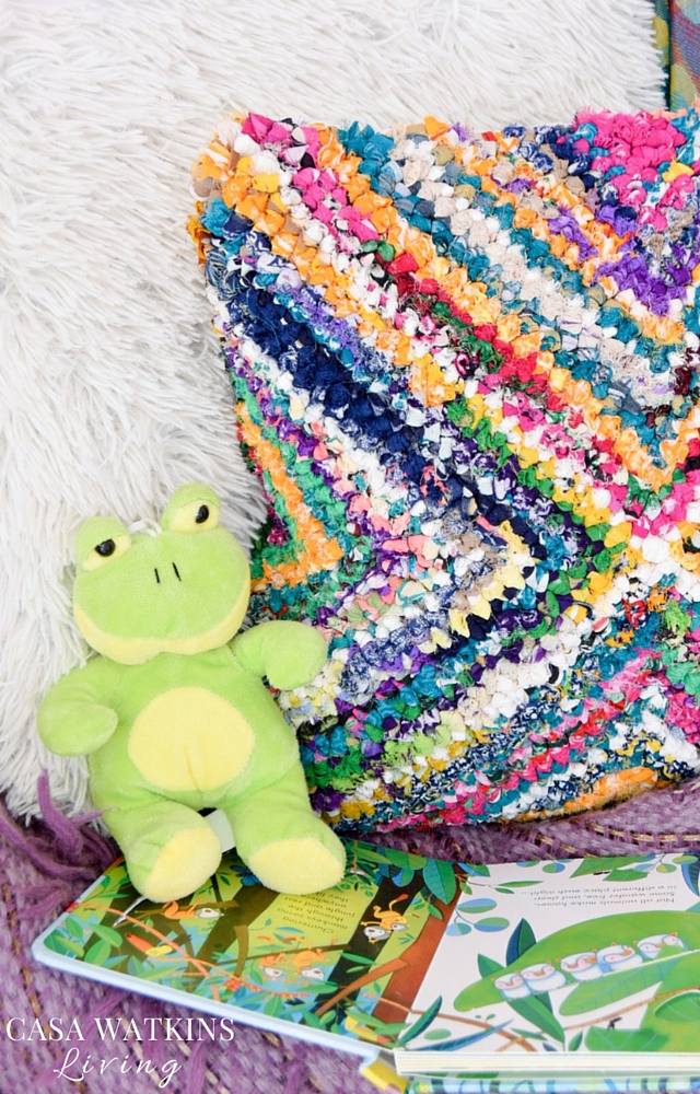 Colorful gathered pillow against faux sheep skin pillow in girl's room