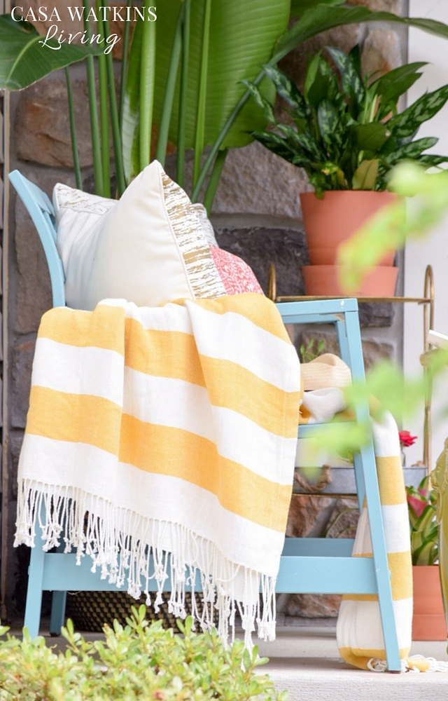 Yellow and white striped blanket with blue outdoor bench