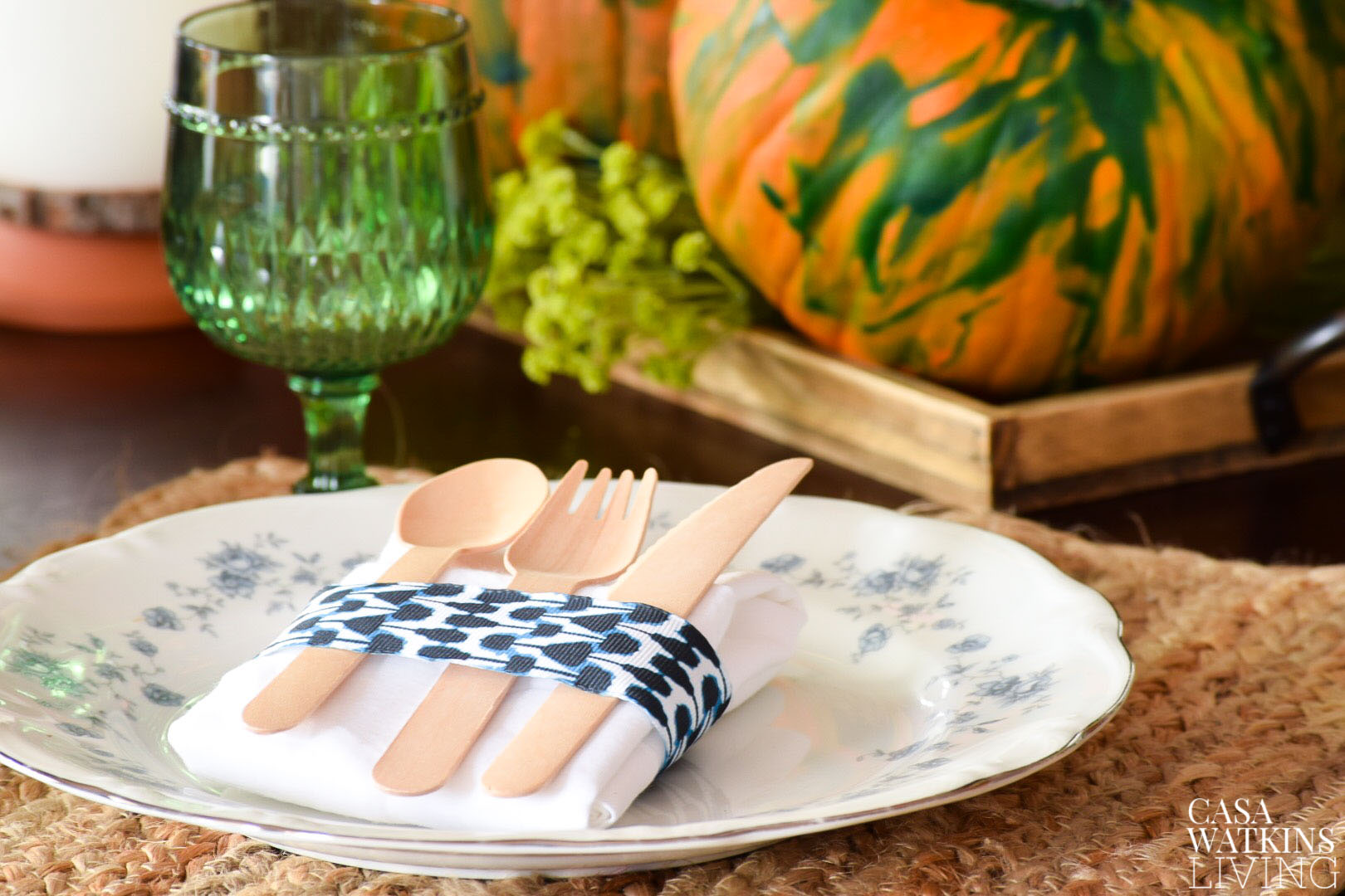 shibori ribbon around white napkin and wooden cutlery