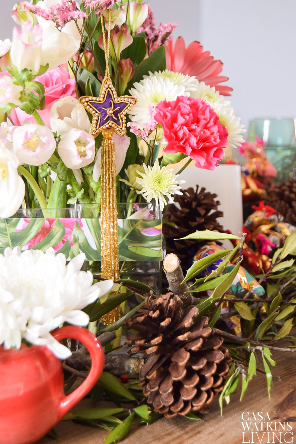 Use hanging ornaments on floral centerpiece for holiday decor