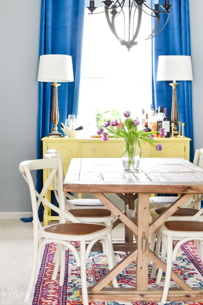 blue global eclectic dining room with velvet drapes and farmhouse table