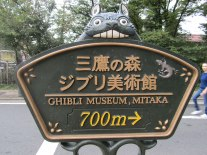A sign featuring a peeking Totoro points the way to Mitaka City's Studio Ghibli Museum