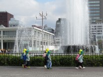 Schoolkids walk by the Fountain of Prayer, commemorating those who died from their burns while begging for water.