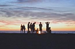 People enjoying a Cascadian Summer bonfire as the sun sets.