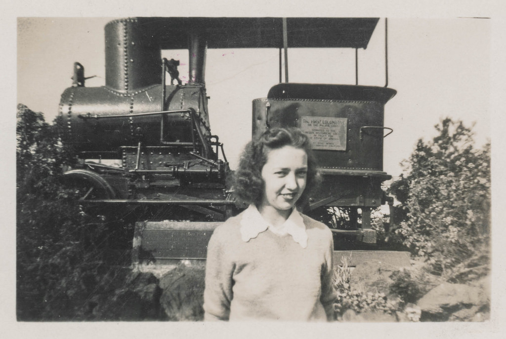 The Oregon Pony, first locomotive in the Pacific Northwest, sits unrestored with a young woma posing in the foreground.