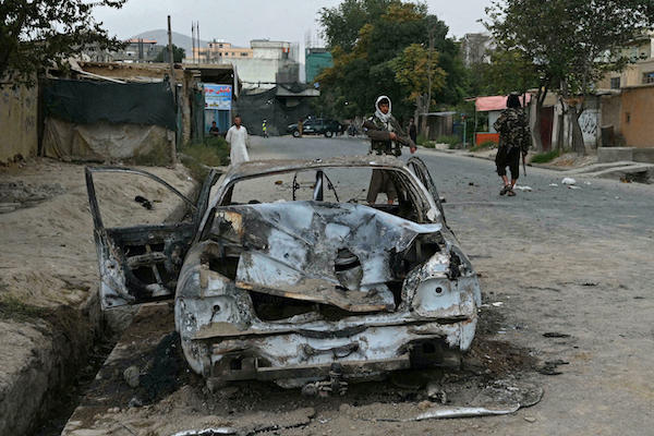 Taliban by burned out car