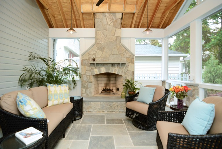 screened-in porch addition natural wood ceiling flagstone floor fireplace pendant lights