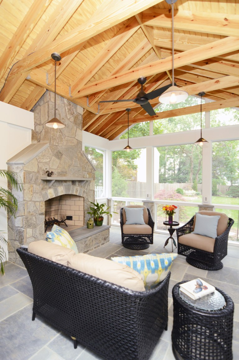 screened-in porch addition natural wood ceiling flagstone floor fireplace with ceiling fan pendant lights