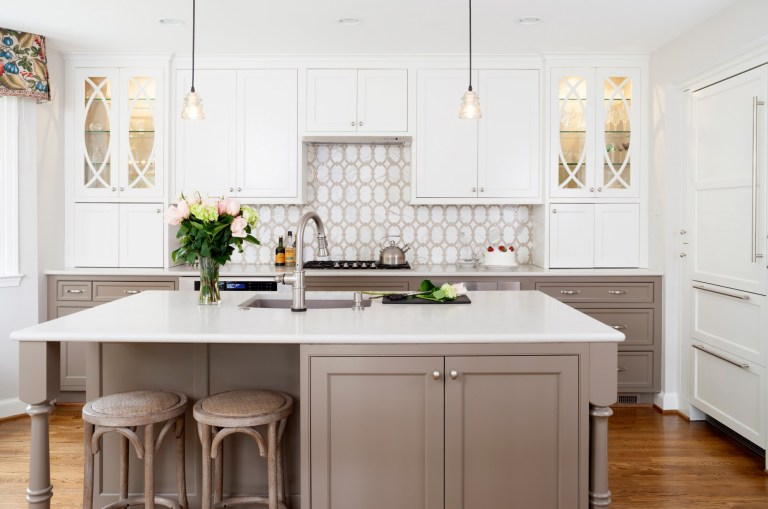 bright kitchen with neutral color palette island with seating and pendant lighting geometric backsplash