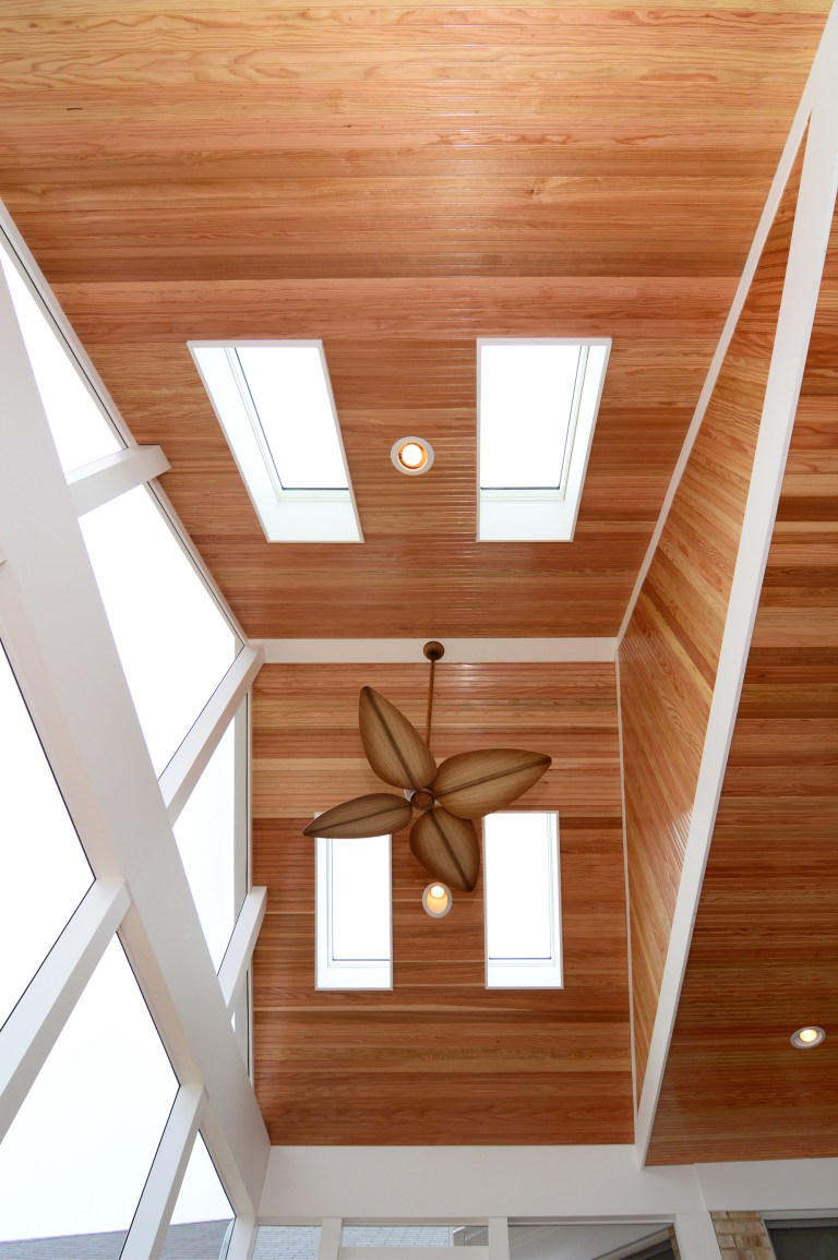 vaulted wood ceilings with skylights ceiling fan and recessed lighting