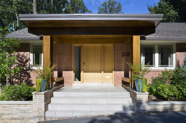 modern brick home new front porch with wood columns and overhang stone foundation mixed materials