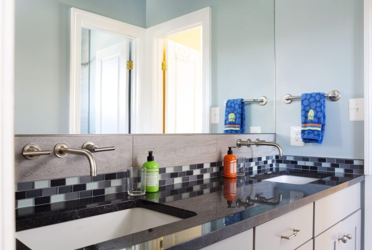sleek updated bathroom tile backsplash and wall mounted faucets blue color palette