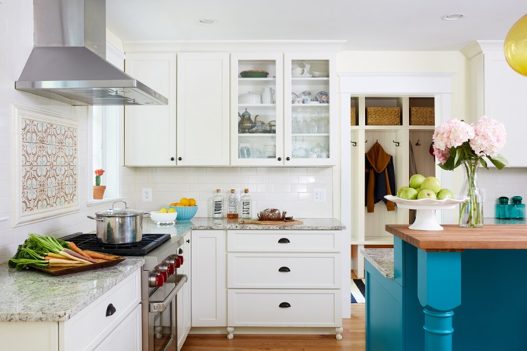 white kitchen with teal island glass door upper cabinets wood floors