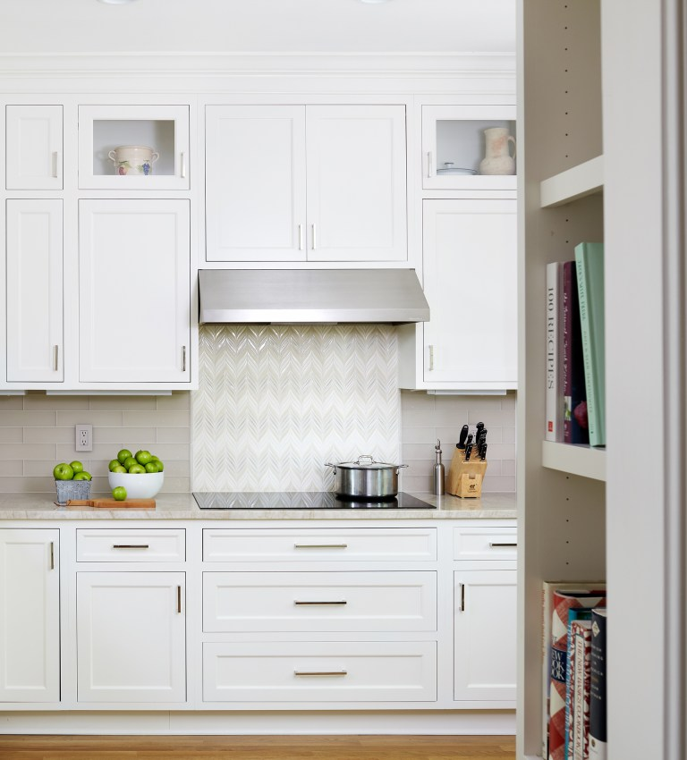 electric stovetop and stainless steel hood with backsplash tile detail