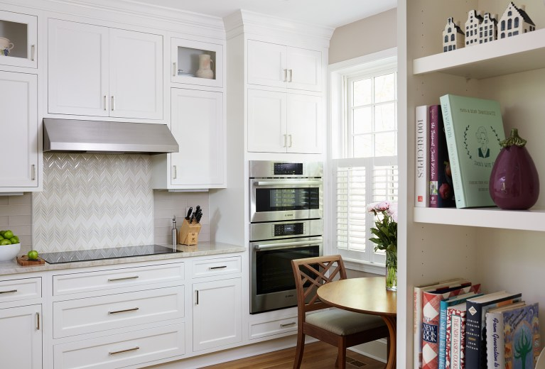 electric stovetop and stainless steel hood and wall oven with backsplash tile detail