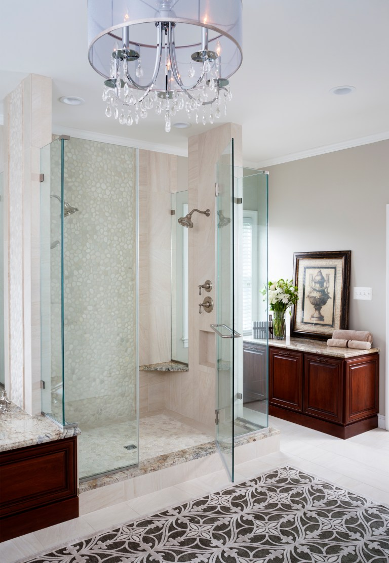 view of master bathroom shower chandelier and cabinet area