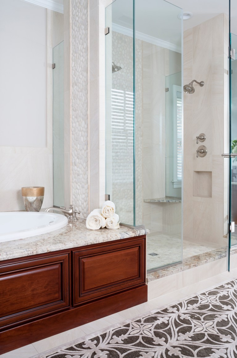 wood paneled bathtub separate shower stall with glass wall built in bench and wall nook