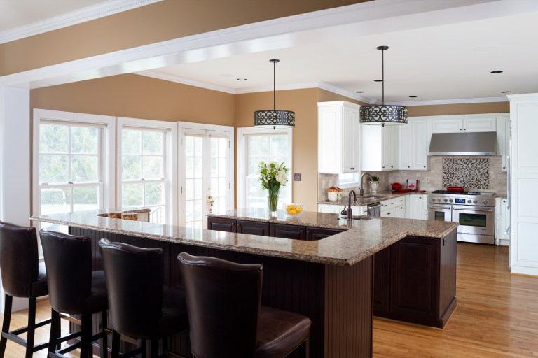kitchen with beige walls lots of windows island with dark wood cabinetry and bar height seating