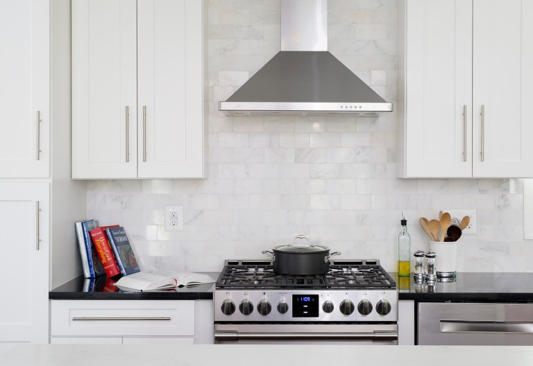 stainless steel gas range and hood subway tile backsplash
