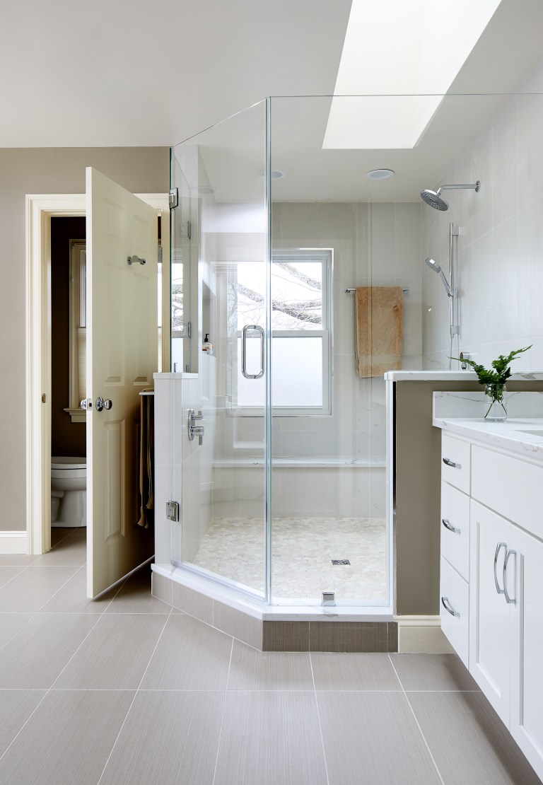 master bathroom with separate water closet large shower two sinks and skylight