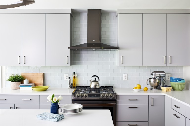 white and gray cabinetry dark stainless steel appliances glass subway tile backsplash