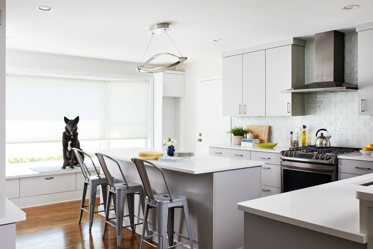 bright modern kitchen white outer cabinetry gray island bay window with built in seat