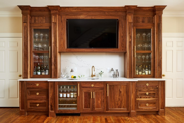 Wet bar with tv above and wood cabinets, wine fridge and sink