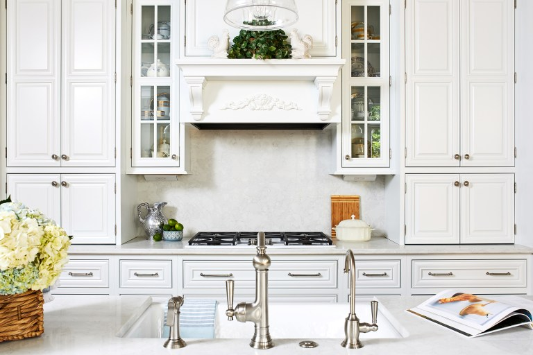 kitchen remodeling with large white tall cabinets with silver knobs and white hood range above stove plate
