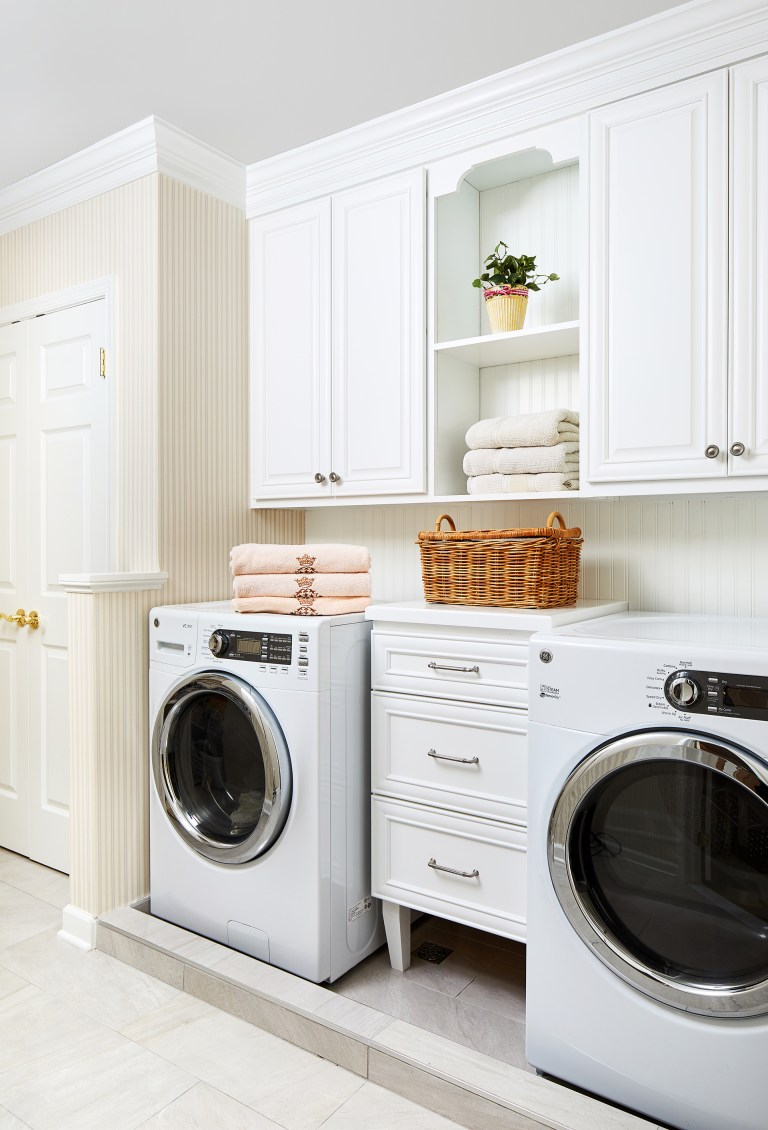 white modular laundry room storage set with accessories in white with some open shelving with basket