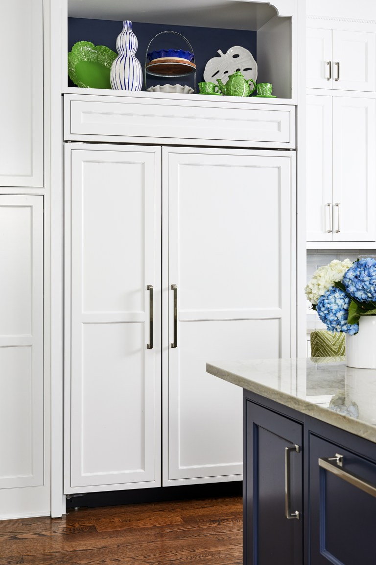 white kitchen wood panel hidden French door refrigerator with pull handles surrounding white cabinets