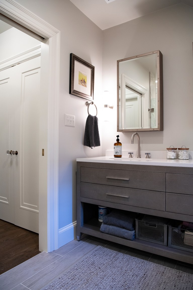 bathroom with gray cabinetry open shelving soft color palette