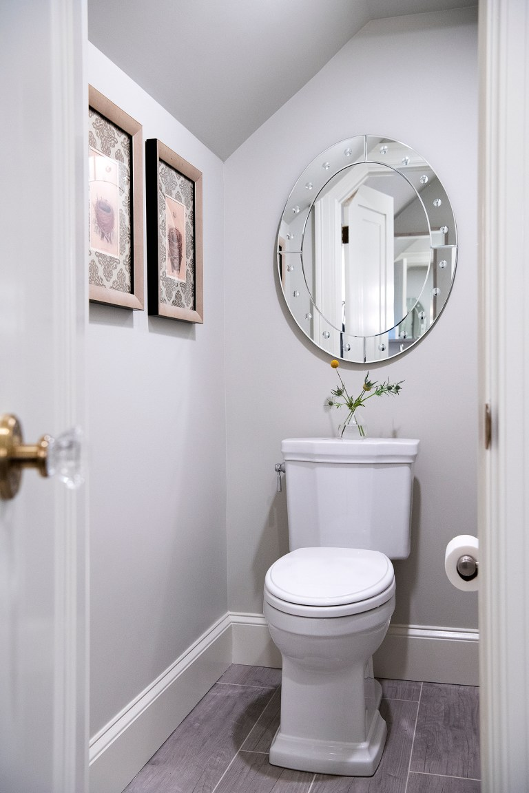 small transitional bathroom with grey walls, grey tiles flooring with oval mirror above toilet