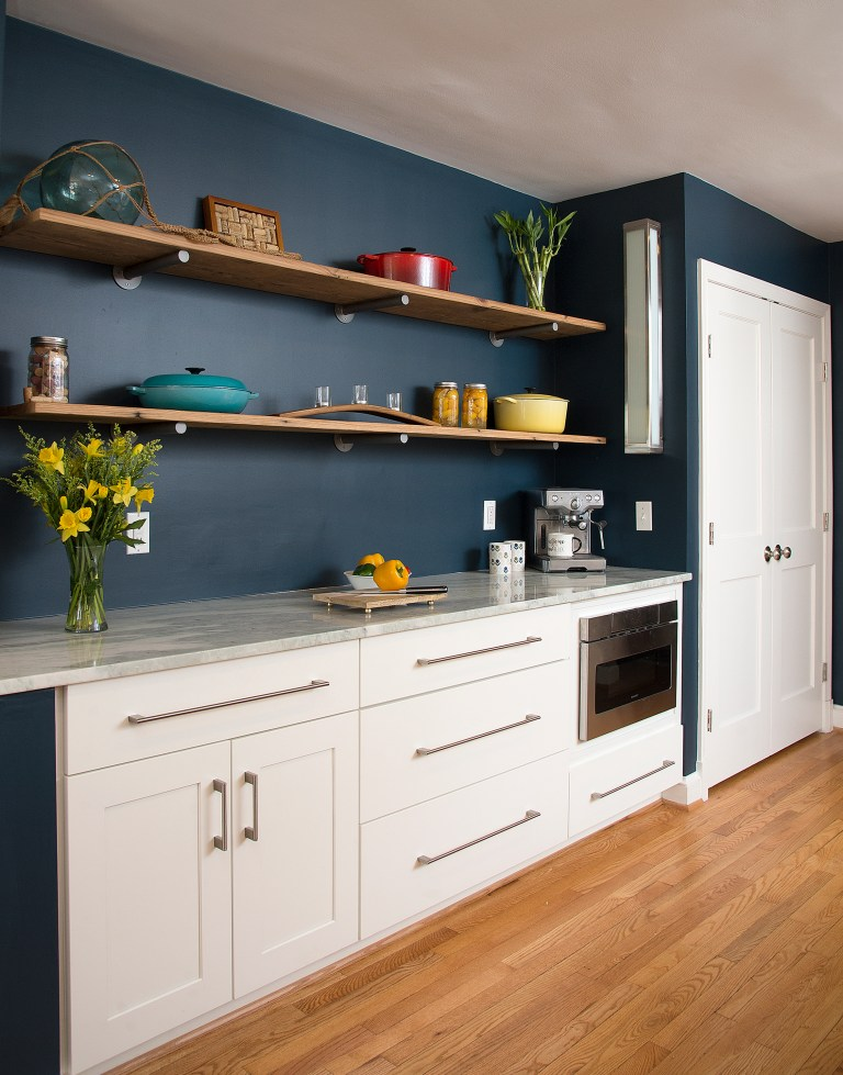 kitchen with navy walls white cabinetry open shelving