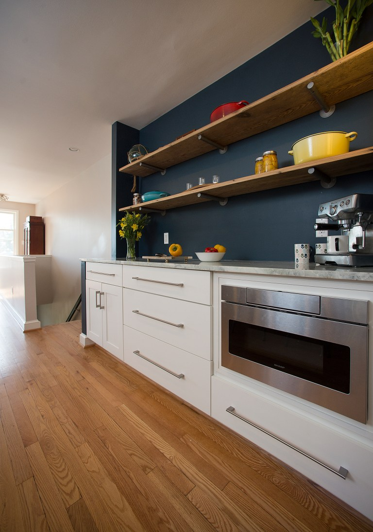 kitchen with navy walls white cabinetry open shelving stainless steel appliances
