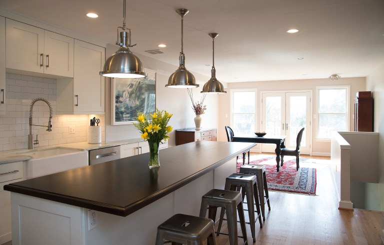 kitchen island with seating and black countertops and open side storage pendant lighting