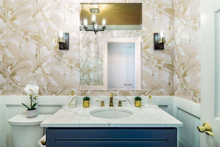 Case design bathroom white counter top and a shimmering golden wall with widespread 2- handle bathroom faucet in brushed gold
