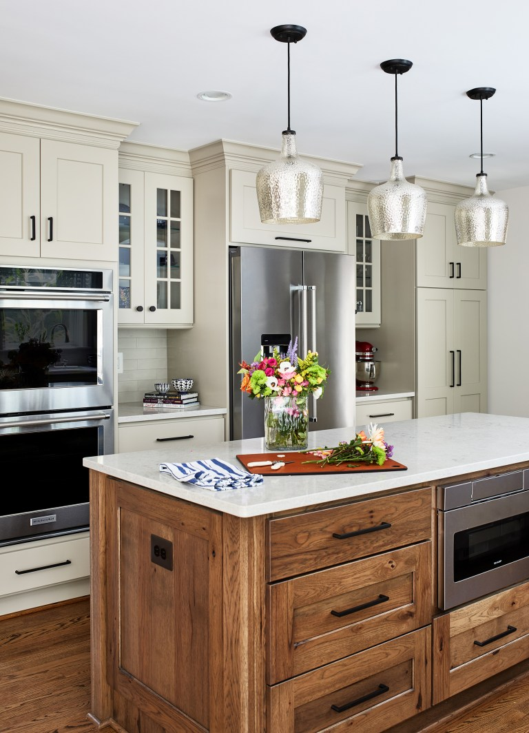 wood kitchen island, subway tiles on the kitchen backsplash with the kitchen island is topped with a slab of white marble