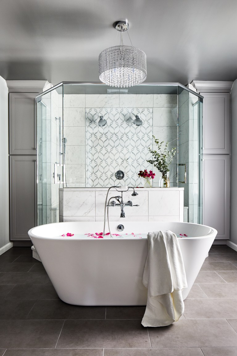 huge crystal chandelier above the white oval bath tub