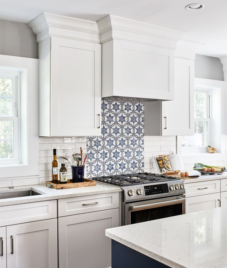 transitional kitchen in VA with 6 burner gas stove, blue/white backsplash and white cabinets with pull handles