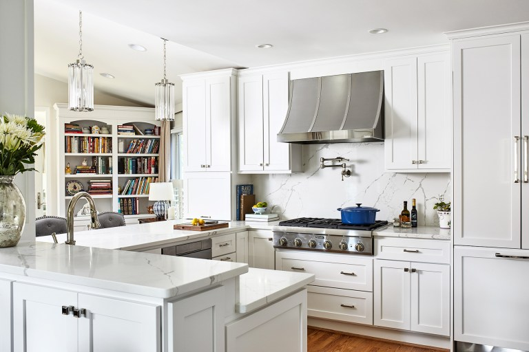 case remodeling kitchen with tall white cabinets with pull handles and hidden refrigerator, hood over your range