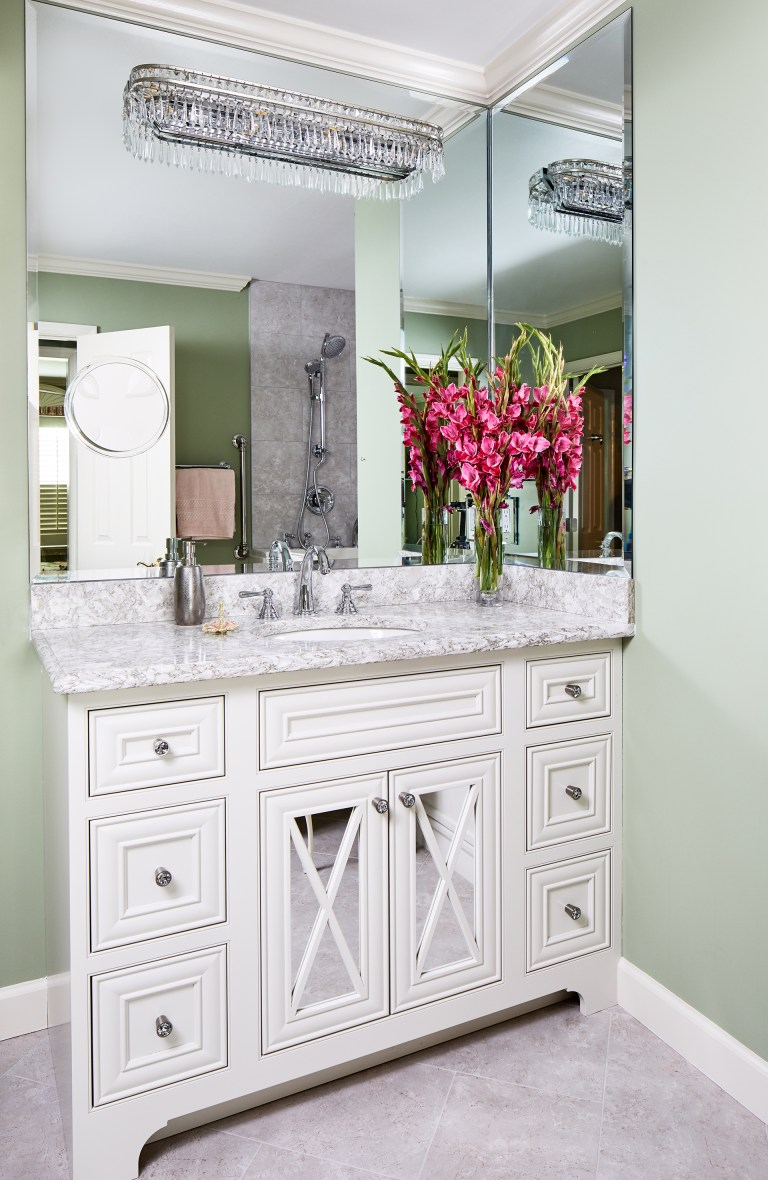 white single sink vanity, marble countertop with two glass doors and huge mirror