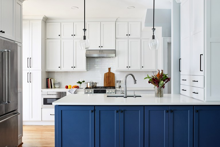 white and blue kitchen with stainless steel appliances, two bell pendant lights, kitchen island with farmhouse sink and floating white cabinets with black knobs